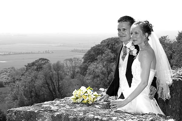 spot colour photo of wedding couple admiring the view from Lympne Castle